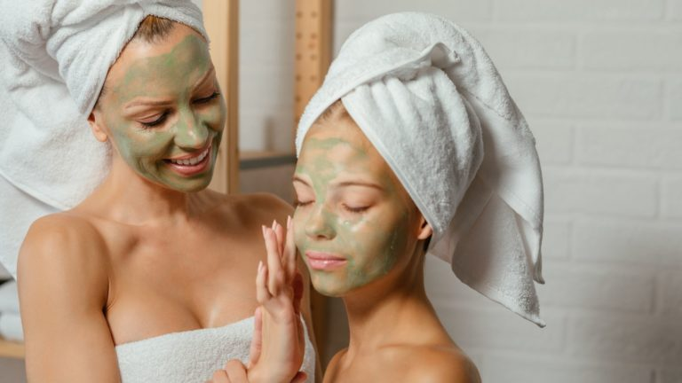 Two women doing face mask
